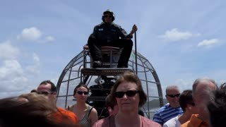 Man working as guide piloting airboat with tourists at Everglades National Park, Florida, USA. American man driving boat