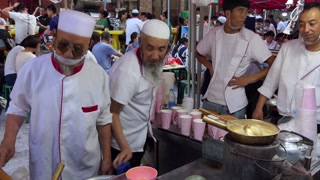 Muslim men working as cook preparing traditional Chinese street food in Lanzhou, Gansu province, China, Asia. Market with stalls and shops selling Asian food. People at work in restaurant kitchen