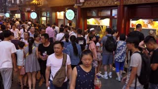Night market, food street in Beijing, China, Asia. Fair with stalls and shops selling Asian food. Chinese people and tourists buying snacks for dinner