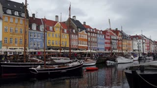 Nyhavn waterfront and entertainment district in Copenhagen, Denmark. Old buildings, homes, houses, townhouses, bars, cafes and restaurants. Canal with historical wooden boats. Tourist attraction