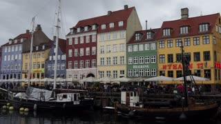 Nyhavn waterfront and entertainment district in Copenhagen, Denmark. Old buildings, homes, houses, townhouses, bars, cafes and restaurants. Canal with historical wooden ships. Tourist attraction