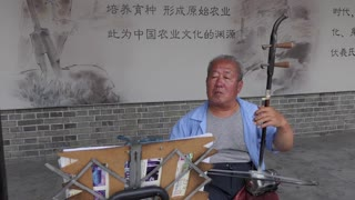 Old Chinese man playing traditional music in Tianshui, Gansu, China, Asia, using musican instrument with strings. Elderly people, tradition, culture, and hobby