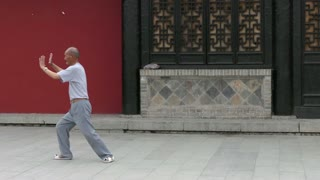 Old Chinese man practicing tai chi martial art for good health and wellness. Elderly Asian people training and working out for wellbeing and fitness in Tianshui, China, Asia