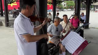 Old Chinese men playing traditional music in Tianshui, Gansu, China, Asia, using musical instruments with strings. Elderly people, senior friends, tradition, culture, and leisure