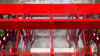 Paddle wheel of tourist steamboat on Mississippi river, leaving trail, ripples and waves on water