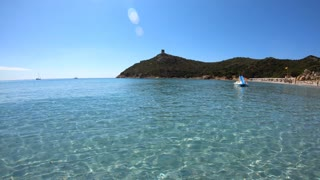People relaxing on holiday in Italy, families and tourists on summer vacations. Italian coast in Sardinia on Mediterranean Sea. Sandy beach in Porto Giunco, Villasimius, Sardegna, Italia