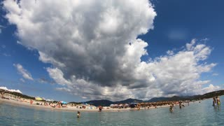 People relaxing on holiday in Italy, tourists on summer vacations. Italian coast in Sardinia on Mediterranean Sea. Sandy beach in Porto Giunco, Villasimius, Sardegna, Italia. Ultra wide angle
