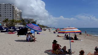 People relaxing on holiday on the beach in Hollywood, Florida, USA. Tourists on summer vacation near the sea. American landscape and recreation in America