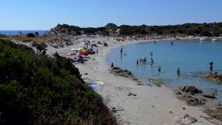 People relaxing on holidays in Italy, tourists swimming during summer vacation. Italian coast in Sardinia on Mediterranean Sea. Sandy beach in Punta Molentis, Villasimius, Sardegna, Italia