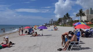 People relaxing on holidays on the beach in Hollywood, Florida, USA. Tourists on summer vacations near the sea. American landscape and recreation in America