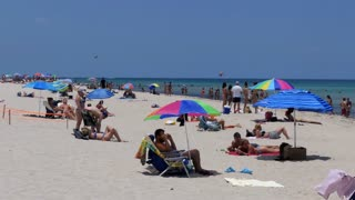 People relaxing on holidays in South Beach, Miami Beach, Florida, USA. Tourists on summer vacations near the sea. American landscape and recreation in America