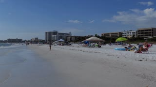 People relaxing on holidays on Siesta Key beach in Sarasota, Florida, USA. Tourists on summer vacations near the sea. American landscape and recreation in America