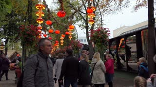 People, tourists, families walking at Tivoli Gardens amusement park in Copenhagen, Denmark during Halloween week