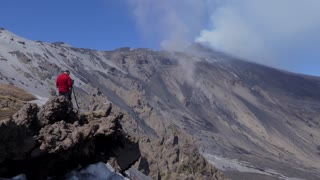 Photographer taking pictures and shooting video of the March 2017 eruption on Mount Etna in Sicily, southern Italy, the largest active volcano in Europe. UNESCO World Heritage site