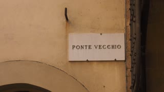 Ponte Vecchio Street Sign And Tourists Walking In Florence