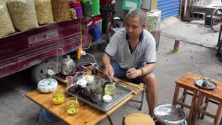 Portrait of a Chinese man serving and selling tea in a small shop at local market in Gulin, China. Traditional culture in Asia