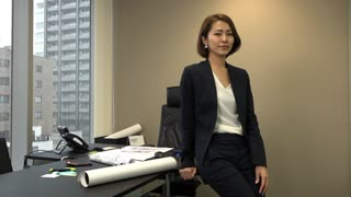 Portrait of Asian people at work in executive office. Beautiful Japanese business woman smiling in corporate studio. Successful businesswoman and happy female manager. Slow motion