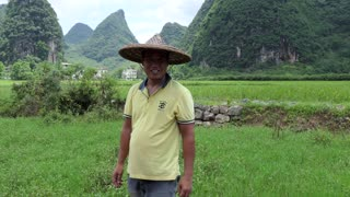 Portrait of Chinese man working as peasant in paddy field in Yangshuo countryside, Guangxi, China, Asia. Happy farmer smiling at camera. Chinese agriculture, farming, rural landscape