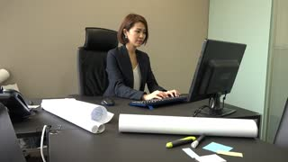 Portrait of happy Asian people at work in executive office. Beautiful Japanese business woman working with computer in studio. Successful businesswoman and female manager smiling at camera