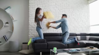 Portrait of Young Couple Playing Pillow Fight