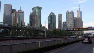 Pudong financial district in Shanghai, China, Asia. Chinese city with modern buildings, road traffic, cars, stock exchange news and weather forecast on display