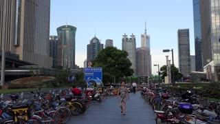 Pudong financial district in Shanghai, China, Asia. Chinese city with modern buildings, tall towers, people walking on sidewalk and parking for bicycles and scooters