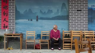 Real elderly Asian people, old Chinese woman from Xianggong hill, near Yangshuo, Guangxi, China, Asia sitting outside a restaurant