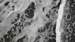 Sea waves breaking on pebble beach. Ocean water along coast and white foam of wave