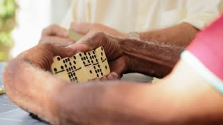 Senior Latino Man Playing Domino With Old Friends