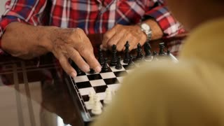 Senior Man And Little Boy Playing Chess Board Game