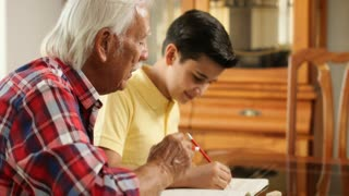 Senior Man Helping Grandson With School Homework At Home