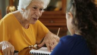 Senior Woman Helping Granddaughter With School Homework