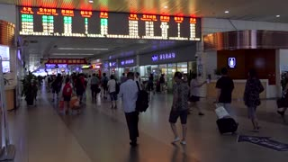 Shanghai Hongqiao Railway Station, China, Asia with crowd, Chinese people and Asian commuters running and walking with suitcases, luggage, bags and baggage