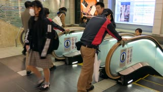 Staff workers cleaning the escalator handrails at Shinjuku JR railway train station in Tokyo, Japan, Asia