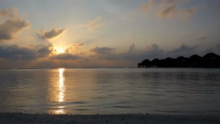 Sunset on Vakarufalhi atoll, Maldives, Asia, Indian Ocean. Holidays in luxury resort. Time lapse with sky, sun, clouds, sea