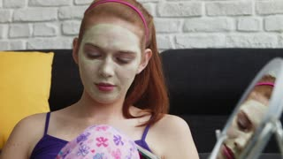 Teenager With Beauty Mask Reading Magazine And Relaxing