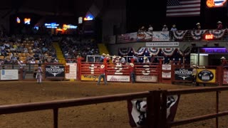 Texan cowboy doing riding bull at rodeo in Cowtown Coliseum, arena in the stockyards of Forth Worth, Texas, United States of America. Man and animal at show