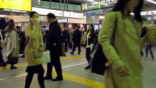 Time-lapse of Japanese people, crowd, commuters in a hurry walking and running at Shinjuku JR railway train station in Tokyo, Japan, Asia during evening rush hour