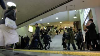 Time-lapse of Japanese people, crowd, commuters walking on stairs at Shinjuku JR railway train station in Tokyo, Japan, Asia during evening rush hour. Underground shopping center with shops, stores