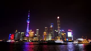 Timelapse of The Bund of Shanghai, China, Asia with Huangpu River at night. Landscape in Chinese city with skyline, modern buildings, skyscrapers, Asian architecture in downtown area