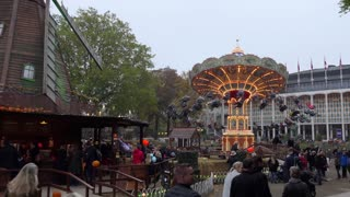 Tivoli Gardens amusement park with people, visitors, tourists, attractions, rides. Urban view of the city of Copenhagen in Denmark, Europe