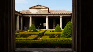 Tourists Visiting Ancient House Garden In Pompeii Italy
