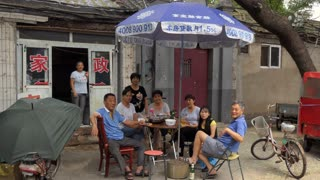 Traditional restaurant in a hutong (old narrow street) of Beijing, China, Asia. Asian people, Chinese family, clients, customers eating local food for lunch