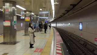 Underground train arriving into Nogizaka subway station in Tokyo, Japan, Asia. Japanese people waiting on platform and Asian commuters traveling