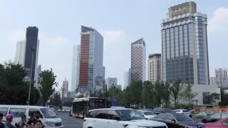 Urban view of Renmin South Road in Chengdu, Sichuan, China, Asia. Landscape in Chinese city with modern buildings, downtown road traffic, cars, bicycles, Asian people walking on the street