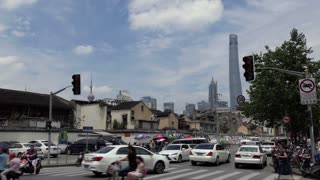 Urban view of Shanghai, China, Asia. Landscape in Chinese city with modern buildings, road traffic, cars, Asian people walking and riding bicycles on the street