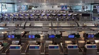 View of Malpensa International Airport in Milan, Italy, Europe. Interior of passenger terminal with people, tourists, travelers at airline check-in counters. Air transportation travel in Milano, Italia