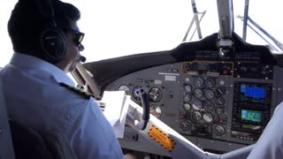 View of the cockpit of a small airplane flying in the sky. Pilot on plane and crew touching equipment on dashboard. Aviation, travel, job, profession