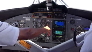 View of the cockpit of a small airplane flying in the sky. Team of pilots on plane, crew touching equipment and commands on dashboard. Aviation, travel, job, profession