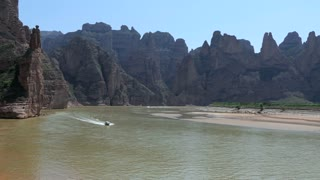 View of the Yellow River near Bingling, Gansu province, China, Asia. Boat, mountains, natural landscape, water, nature and countryside